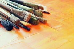 Bästa sikt av uppsättningen av använda målarfärgborstar över trätabellen Royaltyfri Foto