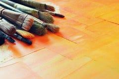 Bästa sikt av uppsättningen av använda målarfärgborstar över trätabellen Arkivbild