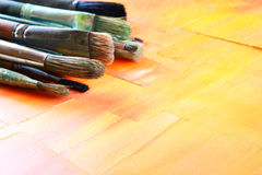 Bästa sikt av uppsättningen av använda målarfärgborstar över trätabellen Royaltyfri Bild