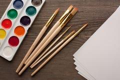 Bästa sikt av vattenfärgmålarfärger, borstar och vitark av papper fotografering för bildbyråer