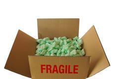 Bästa sikt av wellpappasken med ordet BRÄCKLIGT som fylls med stycken av grönt plast- skum royaltyfria foton