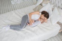BÄSTA SIKT: Barnet som modern ligger på en säng med hennes litet, behandla som ett barn Royaltyfria Bilder