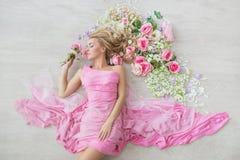 BÄSTA SIKT: Den härliga unga kvinnan i en rosa klänning ligger på ett golv med blommor Royaltyfria Bilder