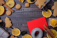 Bästa sikt för jul över en brun träbakgrund med gåvaaskar som packas i ett hantverkpapper med färgad apelsiner, kakor och christm royaltyfri foto
