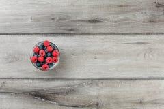 Bästa sikt för tabell på den lilla glass bunken mycket av blåbär och raspb royaltyfri bild