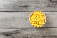 Bästa sikt för tabell på snitt för rå potatisar i små stycken i beige bunke arkivfoto