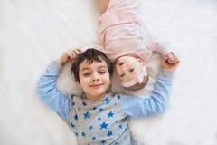 BÄSTA SIKT: Gullig broder med hans lilla syster på en säng Arkivfoto