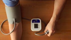 BÄSTA SIKT: Händer av den unga mannen som mäter blodtrycket - nära övre Fotografering för Bildbyråer