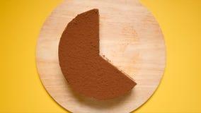 BÄSTA SIKT: Halva av chokladkakan på en gul bakgrund Arkivbild