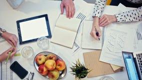 Bästa sikt - kontorsskrivbord med apparater och legitimationshandlingar på affärsmötet av arbetslaget lager videofilmer