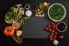 Bästa sikt, lekmanna- lägenhet Ingredienser för framställning av fransk traditionell niçoisenicoisesallad runt om en svartstensk royaltyfri fotografi