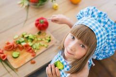 BÄSTA SIKT: Lilla flickan i kockkläder äter en gurka och ser till kameran Arkivbilder