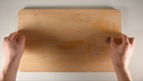 BÄSTA SIKT: Mänskliga händer sätter den stora skärbrädan på en vit tabell Arkivbilder