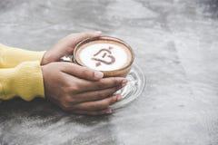 Bästa sikt med kopieringsutrymme Handkvinnor som rymmer händer med kaffeförälskelse på tabellen, tappningsignal Royaltyfri Foto