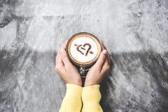 Bästa sikt med kopieringsutrymme Handkvinnor som rymmer kaffeförälskelse på cementtabellen, tappningsignal Royaltyfri Bild