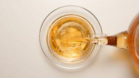 BÄSTA SIKT: Nytt te som flödar till en tekopp från en tekanna Royaltyfri Bild