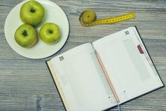 Bästa sikt på den öppnade anteckningsboken och blyertspennan, tlape med äpplen på den arkivbild