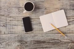 Bästa sikt på den öppnade anteckningsboken, smartphonen, highlighters och annan utrustning på träkontorsskrivbordet, gamla plancs fotografering för bildbyråer