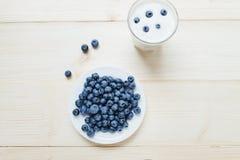 Bästa sikt på den lantliga sunda frukosten med blåbäret och yoghurt i ett exponeringsglas på en trätabell Exponeringsglas av heml Royaltyfri Foto