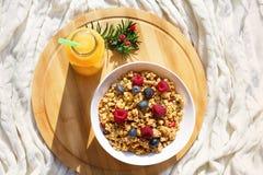 Bästa sikt på den sunda frukosten med granola och bär i den vita bunken och ny orange juce på det runda trämagasinet på stuckit h royaltyfria bilder