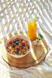 Bästa sikt på den sunda frukosten med granola och bär i den vita bunken och ny orange juce på det runda trämagasinet på stuckit h arkivbild