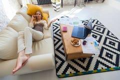 Bästa sikt på den unga kvinnan som ligger på sängen med den bärbar dator-, telefon- och fotokameran Vila efter arbetet 2 business Arkivbilder
