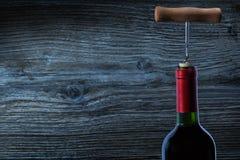 Bästa sikt på flaskan av rött vin och corckscrew royaltyfri bild