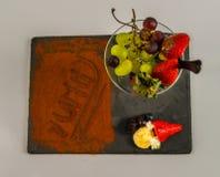 Bästa sikt på frukter i exponeringsglas och ordet som är smaskigt på den svarta stenen pl Royaltyfri Foto