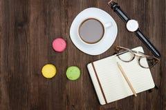 Bästa sikt på koppen kaffe, macarons, anteckningsboken, klockan och exponeringsglas Arkivbilder