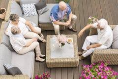 Bästa sikt på möte av aktivt äldre folk på terrass med flo fotografering för bildbyråer