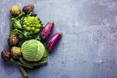Bästa sikt på nya grönsaker som ordnas runt om gränsen på grå kökcountertop royaltyfri foto