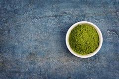 Bästa sikt på organiskt grönt pulver för ½ för matchateaï¿ på blå konkret bakgrund royaltyfri bild