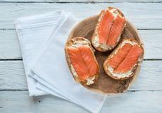 Bästa sikt på smörgåsar med laxen och gräddost på en vit trätabell Fotografering för Bildbyråer