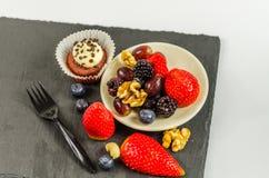 Bästa sikt på uppsättning av olik muttrar och frukt med chokladmuffin Fotografering för Bildbyråer