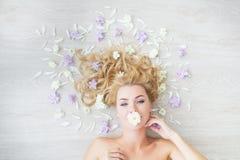 BÄSTA SIKT: Ståenden av den caucasian blonda flickan med blomman i en mun på ett golv med ett fält blommar Fotografering för Bildbyråer