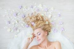 BÄSTA SIKT: Ståenden av den caucasian blonda flickan med de stängda ögonen på ett golv med ett fält blommar Arkivbilder