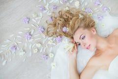 BÄSTA SIKT: Ståenden av den nätta blonda flickan på ett golv med ett fält blommar Arkivbild