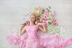 BÄSTA SIKT: Ståenden av en härlig ung flicka i en rosa klänning ligger på ett golv med blommor Royaltyfria Foton