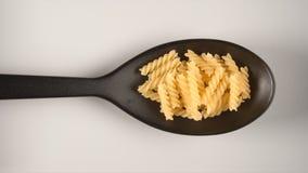 BÄSTA SIKT: Svart sked med spiral pastafusilli Arkivbilder