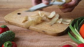 Bästa skott av bitande potatisar för mankock på skärbräda lager videofilmer