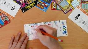 Bästa skott av mannen som fyller lyckligt nummer på maximal biljett för lotto stock video