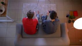 Bästa skott av två vänner i sleepwear som spelar videogamen som använder tillsammans styrspaken och ger fem i vardagsrummet arkivfilmer