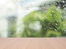 Bästa tom wood tabell på suddig abstrakt vattendroppe på exponeringsglas Royaltyfri Bild