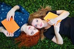 Bästa vän är kvinnliga studenter på gräsmatta Royaltyfri Foto
