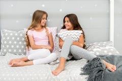 Bästa vän eller syskon för flickor lyckliga i gullig stilfull pyjamas med kuddesleepoverpartiet Systrar som har den roliga sleepo royaltyfri bild