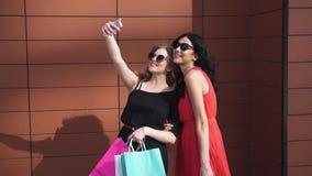 Bästa vän gör selfie, når de har shoppat härliga flickor i solglasögon med shoppingpåsar i handen som tar bilder och stock video
