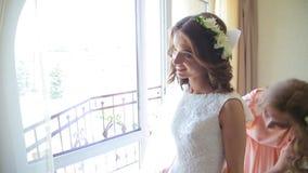 Bästa vän hjälper den framtida bruden att bära en bröllopsklänning stock video