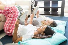 Bästa vän i pyjamas som tillsammans ligger och läser romaner royaltyfria bilder
