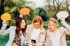 Bästa vän som rymmer en komisk ballong, förvånas om något såg precis på smartphonen fotografering för bildbyråer
