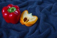 Bästa veiw av en röd peppar och halv orange peppar på en blå bakgrund Royaltyfri Foto